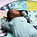 baby laying on mint play mat