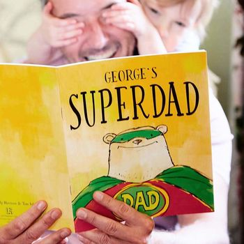 personalised super dad superhero story book held by dad and child