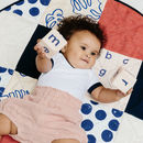 baby laying on peach navy patchwork play mat