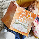 little girl smiling reading a personalised childrens story book about the family dog
