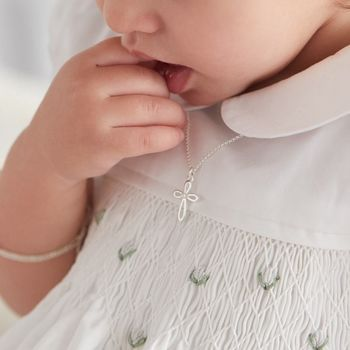 Baby modelling the Cherish Pearl Cross