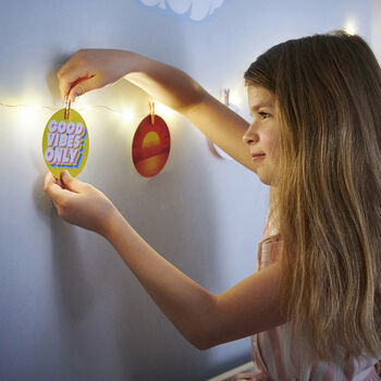 Girl pegging up Can-Do Positivity card on fairy lights
