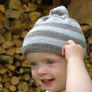 Baby wearing bobble hat in blue and pebble grey