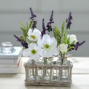 Faux White And Lilac Blooms In Country Wicker Bottles