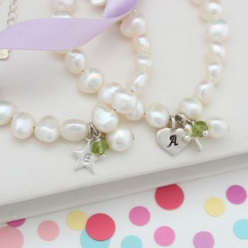 childs white pearl christening bracelet with peridot for august birthdays and silver letter charm