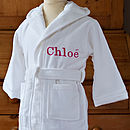 White bathrobe with fuchsia embroidery.