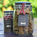 Thumb hand baked dog biscuits in storage jar