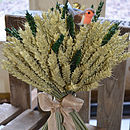 Christmas wheat sheaf with natural wheat and green wheat. Decorative ribbon in gold and robin decoration