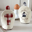 personalised egg cosies, cream with red initial and cream with blue initial