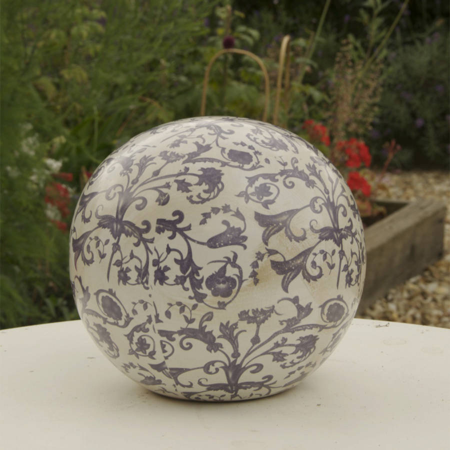Blue and white aged ceramic decorative ball by the orchard