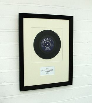 Framed 7-inch vinyl single mounted in black wood frame
