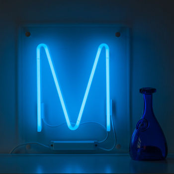 Blue neon 'M' sandwiched between clear perspex