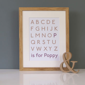 alphabet print with text in old rose and plum in an oak frame