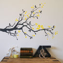 dark grey branch with yellow birds